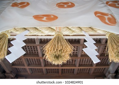 Wide close-up of straw shimenawa rope, paper shide charms, and cloth decorated with the tomoe symbol at a Japanese Shinto shrine. Nobeoka, Kyushu, Japan. Travel and religion concept.