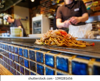 Wide closeup of Yakisoba cooked on a teppan grill, topped with Katsuobushi fish flakes and sauce. Shallow focus. Dotonbori, Osaka, Japan. Travel and cuisine.
