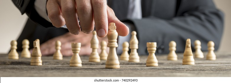 Wide cropped image of a businessman playing chess reaching white king piece for concept about overcoming difficulty and achieving goals.