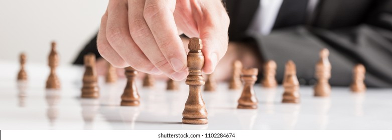 Wide cropped image of businessman wearing business suit moving dark King chess piece at white table.