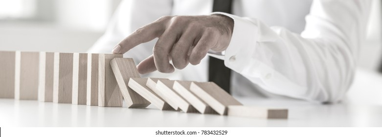 Wide cropped view of a businessman stopping domino effect with his finger. Business crisis concept.