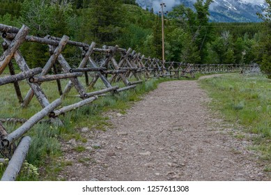Wide Dirt Trail Along Wooden Fence in Tetons