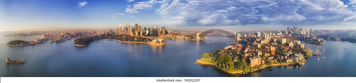 Wide elevated panorama of Sydney city landmarks around blue waters of Harbour on a sunny morning with blue sky reflecting in still waters.