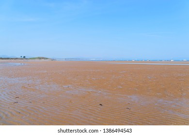 The wide expanse of soft, rippled sand of Llanbedrog beach at low tide reaching down to distant boats on the sea