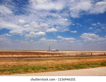 A wide, flat, prairie landscape in the state of Texas, with a vintage traditional windmill, a quonset hut in the middle ground and modern wind turbines far in the background.