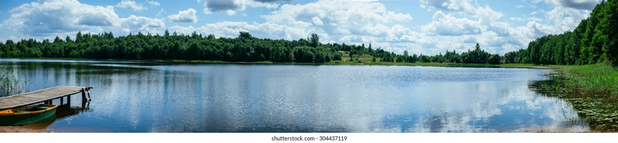 Wide forest lake with a swimming pier on a sunny day