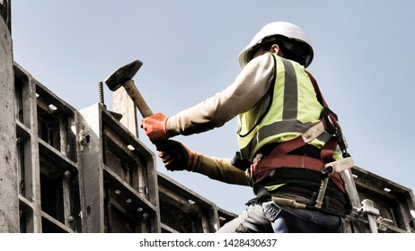 Wide format image of a construction worker holding hammer in the air