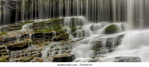 Wide format panorama of waterfall crashing over rocks and moss
