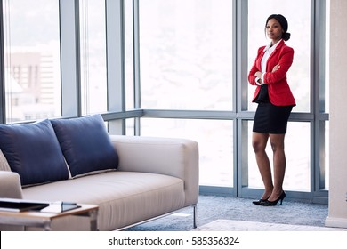 Wide full body shot of business woman standing next to large windows in a business lounge, with confident body language and her arms crossed wearing formal attire