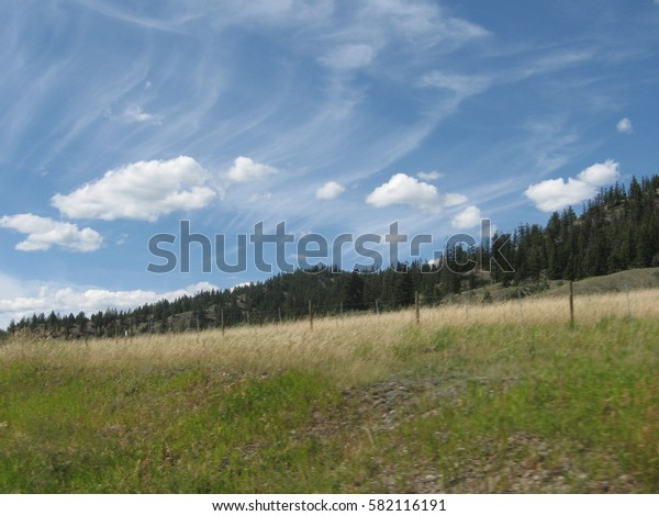 Wide grassy flats of Canadian Chilcotin plateau on a sunny summer day with interesting cloud formations