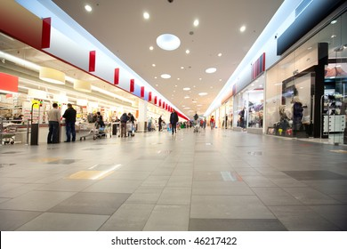 Wide hall and buyers in trading center with shops on both sides