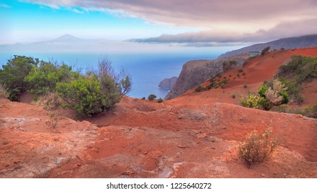 """wide, high above """"Agulo"""" landscape with dark red earth, bright and mysterious. Some crippled heather plants can be seen, otherwise only the blue Atlantic Ocean and in the distance the """"Teideview""""."""