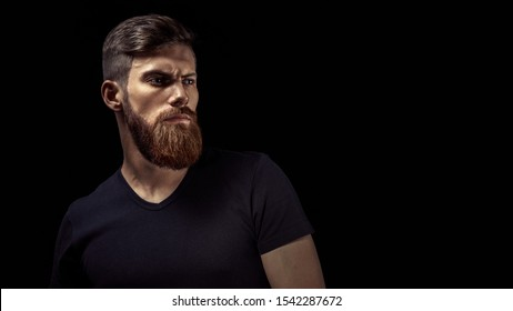 Wide horizontal portrait of serious young stylish bearded male model  on black background Confident concept Free copy space for text Dramatic portrait of young handsome caucasian bearded man