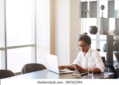 Wide image of young black woman busy holding her credit card in her hand as she makes wire transfers for the online shopping she did on the internet from her dining table at home.