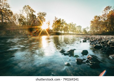 Wide landscape of a calm river during sunrise carrying mist downstream.