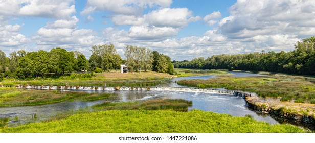 A wide landscape with a river and the widest waterfall in Europe - the Ventas hub (Ventas rumba) in the summer. Latvia.