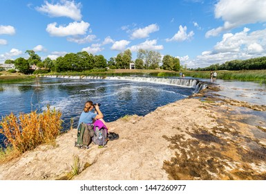 A wide landscape with a river and the widest waterfall in Europe - the Venta hub (Ventas rumba) in the summer. Female photographer, hobby, tourism, recreation. Latvia