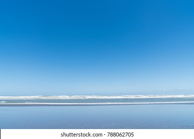 Wide and long image Muriwai Beach sandy beach with water washing in, to distant surf and horizon under blue sky, ideal background scenic image.