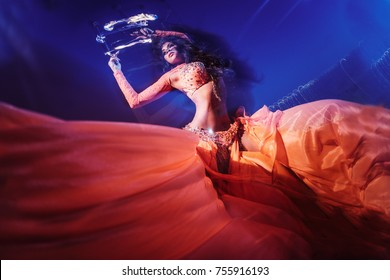 wide and low angle shot of belly dancer with in orange outfit performing with fire at night