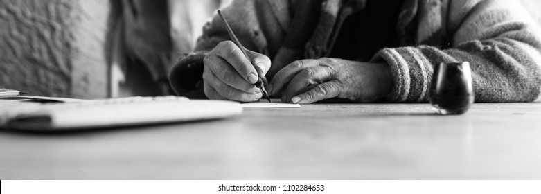Wide low angle view of an elderly man doing calligraphy writing using a nib pen and ink on a sheet of white paper in a monochrome image.
