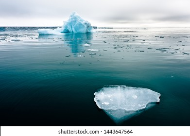 A wide low angle view of melting sea ice floes in still waters of Northern Arctic with iceberg and glacial wall in background.Climate Crisis and Breakdown.Climate emergency.Image