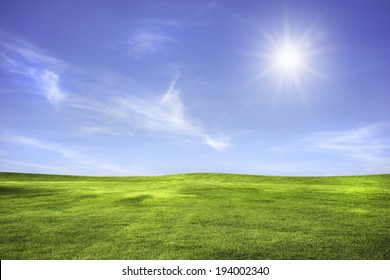 Wide meadow with clouds in blue sky in sunny day