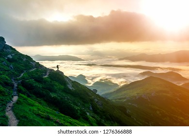 Wide mountain panorama. Small silhouette of tourist with backpack on rocky mountain slope pointing at valley covered with dense white puffy clouds. Beauty of nature, tourism and traveling concept.