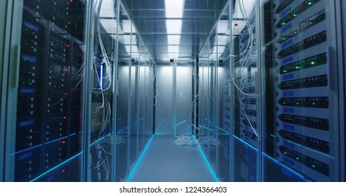 Wide movement stabilized shot forward of an empty corridor in a data center in server room inbetween server racks with a lot of hanging cables