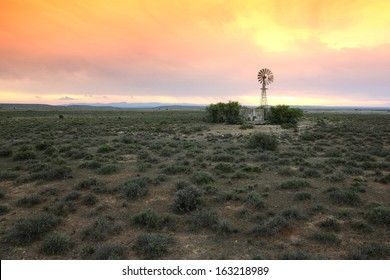 Wide open farm land with a water windmill pump at sunset in the Karoo in South Africa