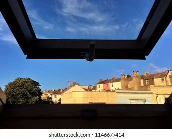 Wide open skylight window full frame looking out from inside seeing sky And rooftops of houses and tree