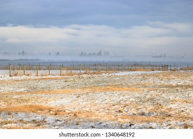 Wide open view of a rural Canadian landscape after a light dusting of snowfall during the early Spring season.