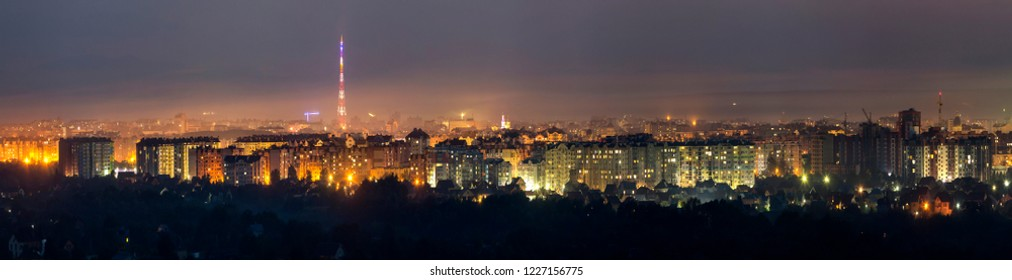 Wide panorama, aerial night view of modern tourist Ivano-Frankivsk city, Ukraine. Scene of bright lights of tall buildings, high television tower and green suburbs.