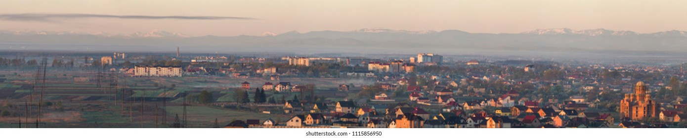 Wide panorama, aerial view of Ivano-Frankivsk city, Ukraine. Scene of modern tourist city with tall buildings, residential quarters and green streets on background of distant Carpathian mountains.