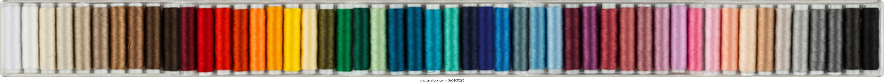 wide panorama background with colorful sewing cottons spools isolated on white background