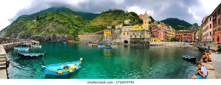 Wide panorama of the beach in Vernazza, with colorful buildings and mountains in the background. Mediterranean landscape, Cinque Terre, Italy, Europe. June, 2018.