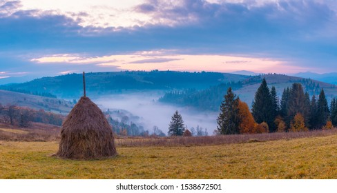Wide panorama of beautiful autumn Carpathian mountains, at early morning, just before sunrise. Beautiful sunrise over mountain foggy valley. Haystack on grassland hill on foreground.