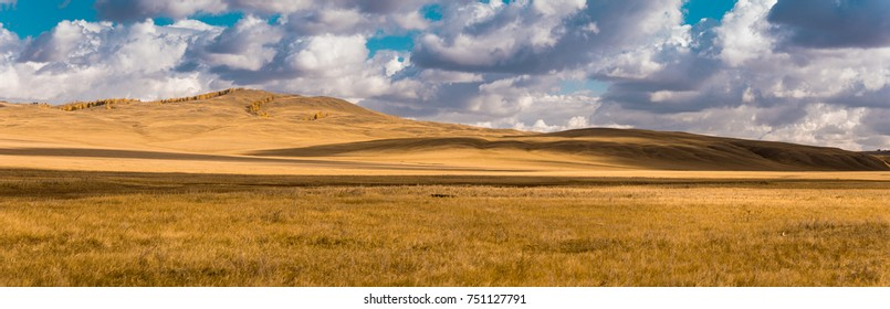 Wide panorama of beautiful autumn field. Majestic open space under dramatic clouds. Kazakh steppe.