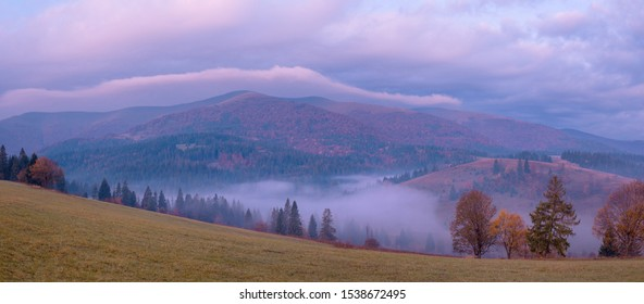 Wide panorama of beautiful autumn foggy Carpathian mountains at early morning just before sunrise.