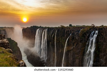 Wide panorama of dreamy victoria falls at sunset with orange sun in the horizon