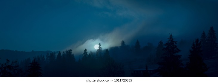 Wide panorama. Full moon through foggy silhouettes of the spruce trees on the mountain hills. Night mysterious landscape in cold tones.