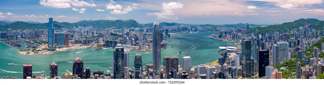Wide panorama of Hong Kong skyline from Victoria Peak on a sunny day