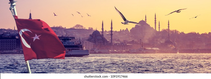 Wide panorama of Istanbul with silhouettes of ancient mosques and minarets at skyline. Panoramic view on medieval city and flight seagulls as travel background with turkish flag and ship in front.