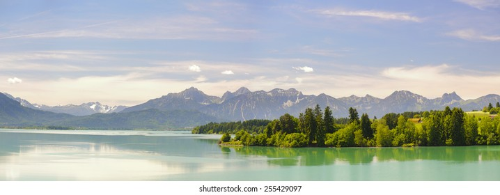 wide panorama landscape with lake Forggensee and alps mountains in Bavaria, Germany, nearby city Fuessen in region allgaeu