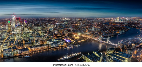 Wide panorama of London, UK, by night: from the City along the Thames river to Tower Bridge and Canary Wharf