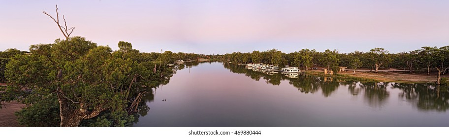wide panorama of Murray river sides in Victoria and New South Wales states of Australia near Mildura regional town. Flat land with green gum trees and floating river houses.
