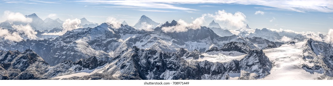 wide panorama on a snowy mountain range of the Swiss Alps