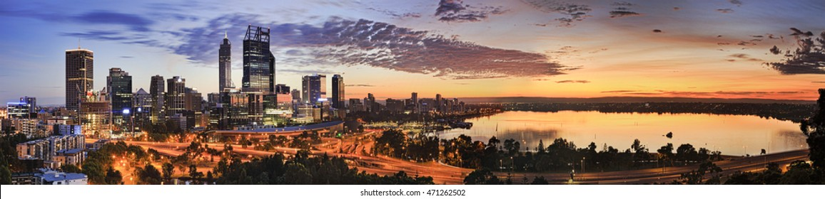 Wide panorama of Perth city CBD as seen from Kings Park lookout at sunrise. Rising orange sun reflects in still waters of Swan river and lights towers of city centre.