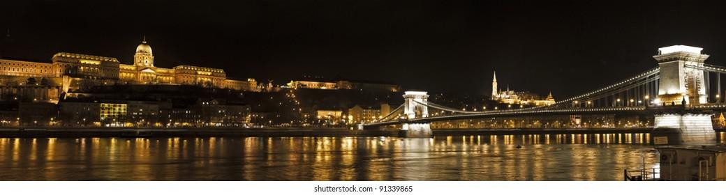 Wide panorama of the river Danube in Budapest featuring the chain bridge (lanchid) Matyas Templom Matthias Church and Budavári Palota (Buda Palace)