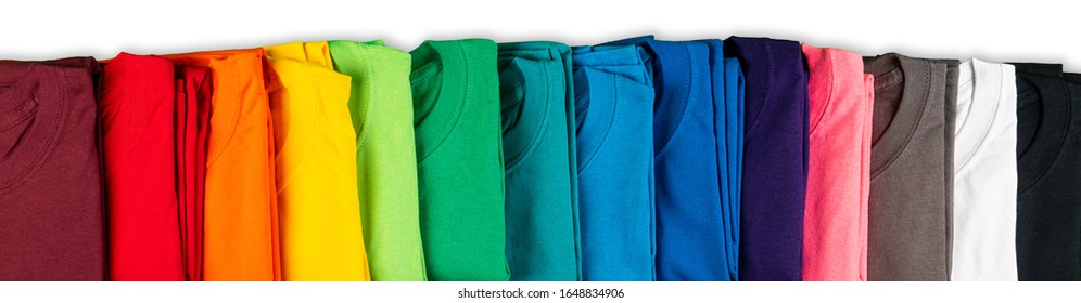 wide panorama row of many fresh new fabric cotton t-shirts in colorful rainbow colors isolated. Pile of various colored shirts on white background