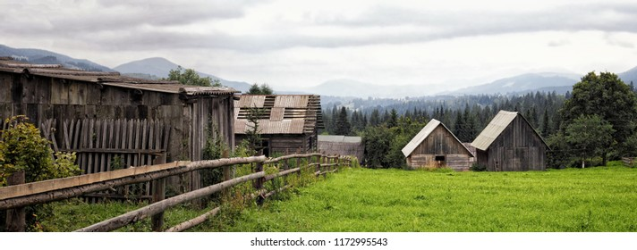 A wide panorama in rural style. Wooden bungalows and barns on a green lawn behind a wooden fence. Mountains and hills covered with forest and gray rain clouds in the background.